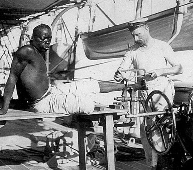British sailor removing the leg irons off a slave late 1800s