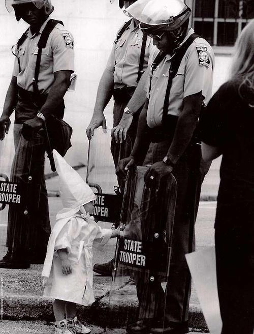 The child of a KKK member approaches black state troopers,1992