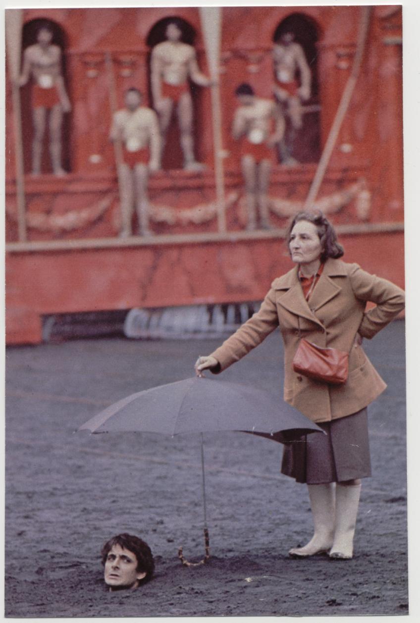 1976. Egy asszisztens tart ernyot a botranyos erotikus thriller a Caligula forgatasa kozben az egyik szereplo feje fole a kivegzesi jelenetben