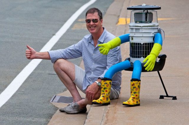 David Harris Smith, assistant professor of communication studies at McMaster, poses for a photo with his latest project, hitchBot.